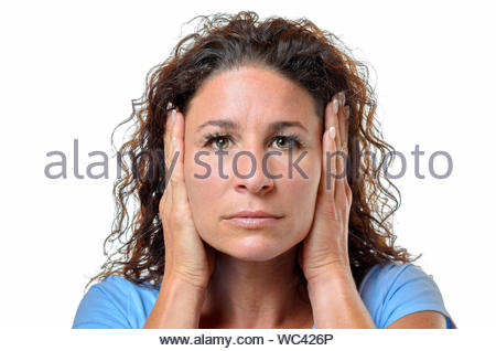 Serious young woman blocking her ears with her hands to avoid hearing something - hear no evil concept isolated on white - Stock Photo