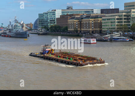 A large barge in the Pool of London, River Thames by HMS Belfast and Hays Galleria on the South Bank of the Embankment, viewed from London Bridge - Stock Photo