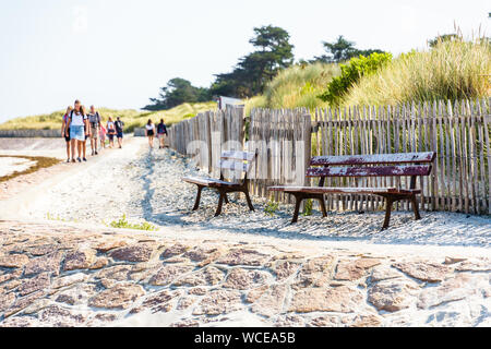 People walking in family or between friends on the GR34 coastal path along the beach in Brittany, on a sunny summer morning. - Stock Photo