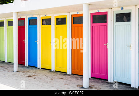 Row of public changing cubicles with colorful doors on the beach of Trestraou in Perros-Guirec, Brittany, France. - Stock Photo