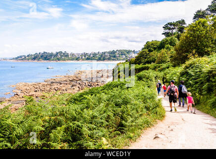 A family with children is walking towards Perros-Guirec on the 'sentier des douaniers', the GR34 coastal path along the Pink Granite Coast in Brittany - Stock Photo