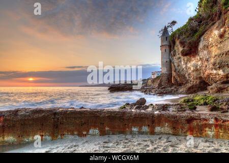Sunset over Pirates tower at Victoria Beach in Laguna Beach, California, USA - Stock Photo