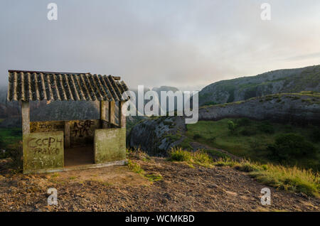 Fog and concrete hut at Black Rocks of Pungo Andongo or Pedras Negras in Angola. These unusual rock formations are of much darker color than their sur - Stock Photo