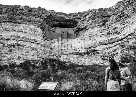 Montezuma Castle on a cloudy day with a couple of visitors trying to figure out where the Sinagua people entered their cliff dwelling. - Stock Photo