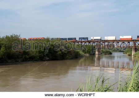 Train crossing the Texas Mexican Railway Bridge over the Rio Grande River on the US Mexico Border. Laredo, Texas and Nuevo Laredo, Tamps. Mexico. - Stock Photo