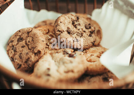 Cookies with chocolate lies in a wicker basket. A basket with gluten free cookies on a wooden table. Selective focus. - Stock Photo
