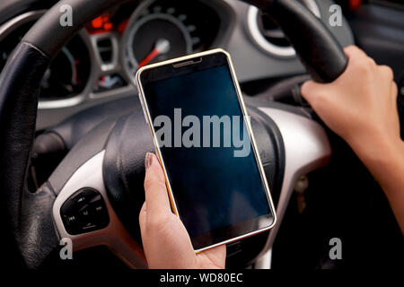 Close up Young female driver using touch screen smartphone and gps navigation in a car, concept using smart phone in car. - Stock Photo