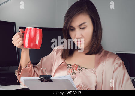Asian woman in satin nightgown drinking coffee to get some energy for working overtime at home - Stock Photo
