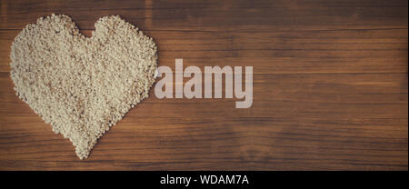 Heart shape made with small white pebbles on a wooden background. Copy space, banner, cover, title - Stock Photo