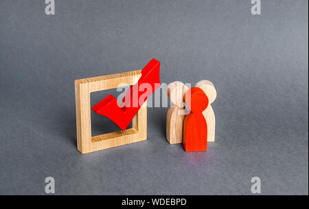 People figurines stand near the checkbox for voting in democratic elections. Lobbying interests, voter bribery, and rigging presidency or parliamentar - Stock Photo