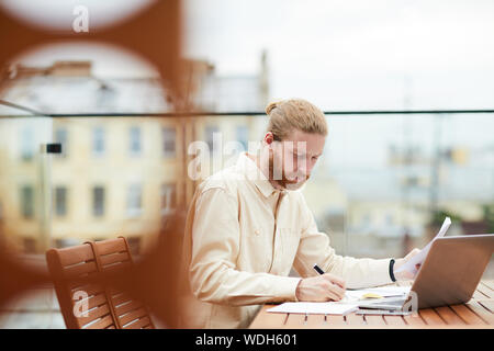 Young bearded man sitting at the table in front of laptop and making notes in document in outdoor coffee shop - Stock Photo