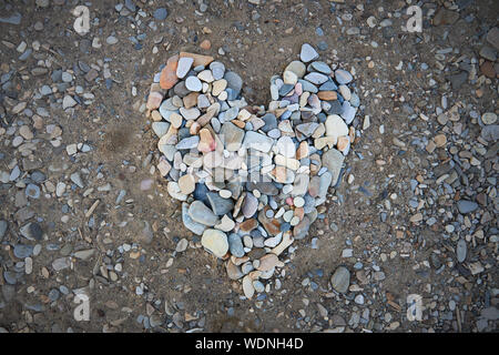 A large heart made of small pebbles on the seashore - Stock Photo