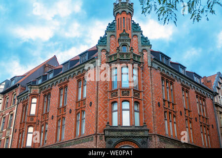 Old red brick building in old town of Hannover next to old town hall - Stock Photo