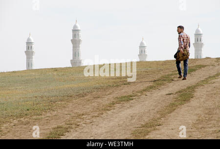 Man walking towards the Hazrat Sultan Mosque in Nur-Sultan, Kazakhstan, while only the four minarets can be seen behind a hill. - Stock Photo