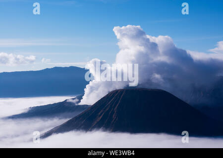 White smoke coming out of volcanoes surrounded by white clouds of mist and a clear blue sky seen at a distance in the afternoon from Mount Penanjakan - Stock Photo