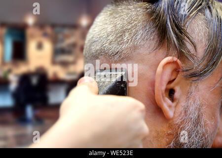 Barber making a haircut using trimmer cutting machine - Stock Photo