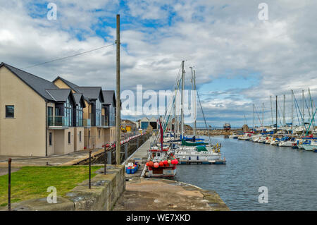 LOSSIEMOUTH MORAY COAST SCOTLAND THE BRANDERBURGH HARBOUR AREA OR MARINA WITH  FISHING BOATS AND YACHTS AND NEW HOUSES ON THE QUAY - Stock Photo