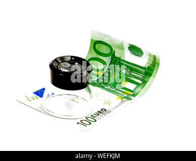 one undred euro bill and lupe on white background - Stock Photo