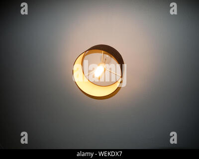bedroom ceiling light turned on electricity white bright; essex; england; uk - Stock Photo