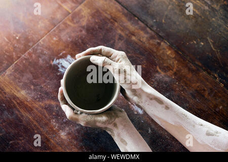 Female hands hold with a wet clay bowl. Pottery making - Stock Photo