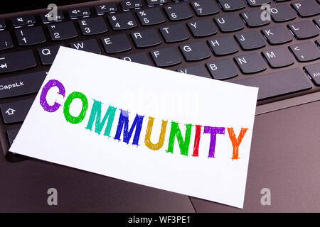Community writing text made in the office close-up on laptop computer keyboard. Business concept for togetherness on the black background with space - Stock Photo