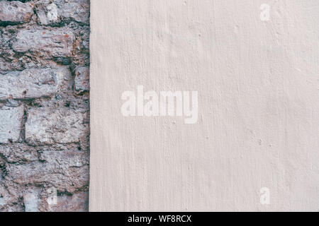 Beige new painted plastered wall with old brick wall background - Stock Photo