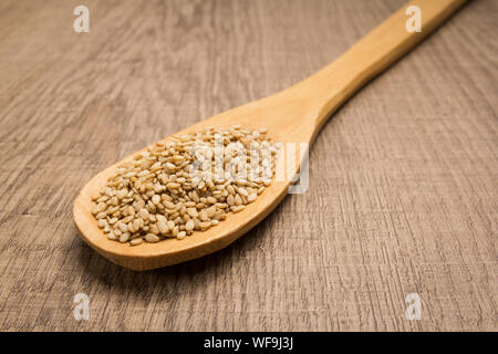 Sesamum indicum is scientific name of Sesame. Also known as Gergelim (portuguese) and Sesamo (spanish). Spoon and grains over wooden table. - Stock Photo