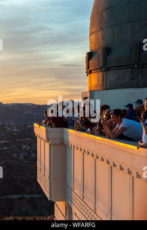 LA, USA - 3rd November 2018: Tourists atop the famous Griffith Observatory take photos of the golden sunset - Stock Photo