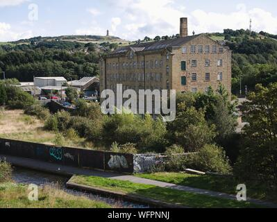 Rear of Folly Hall mill looking across the huddersfield narrow canal and river ex Joseph Lumb now used by the NHS - Stock Photo