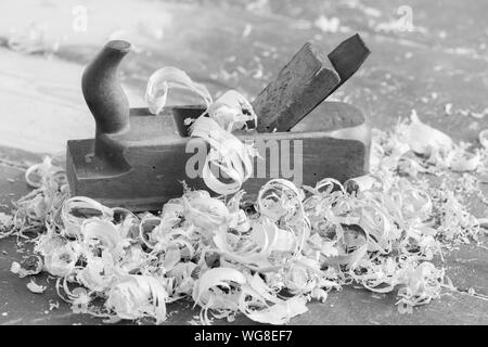 Old wooden hand plane for woodworking with wood shavings. Black and white. - Stock Photo