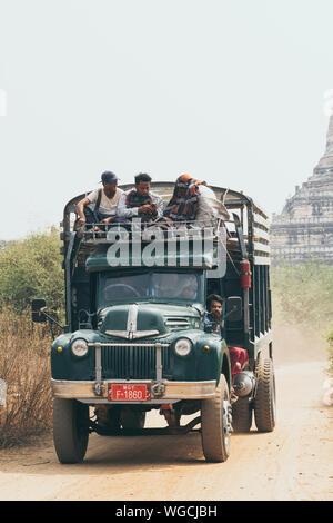 Bagan, Myanmar - March 2019: Burmese men riding retro truck next to Buddhist temple. - Stock Photo