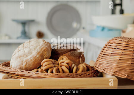 Assortment of breads near a wicker basket on a table in a rustic kitchen. Composition in kitchen at the photo studio - Stock Photo