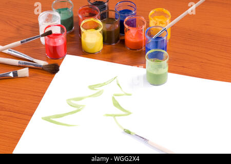Many colorful paints in cans and brushes on table, Christmas tree painted on white paper sheet lying on wooden table, horizontal orientation, nobody. - Stock Photo