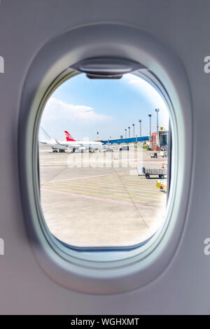 Tbilisi, Georgia, 2019-04-10: view from the window porthole on planes at the airport. Vertical photo - Stock Photo