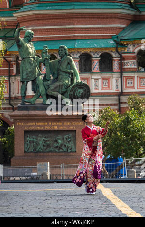 A woman in traditional japanese clothes walks on Red Square during performance of The Japan Ground Self-Defense Force (JGSDF) Central Band in Moscow - Stock Photo