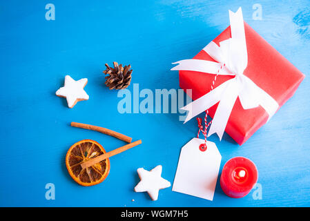 Xmas image with cinnamon sticks, star shaped cookies, dried orange, a lit candle and a lovely red gift tied with white ribbon and bow on a blue wooden - Stock Photo