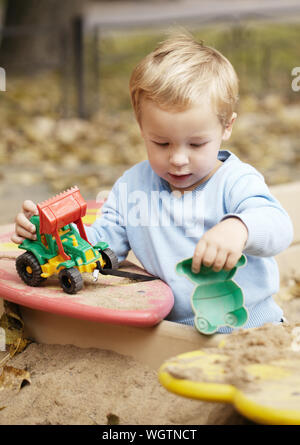 Little boy playing with toy tractor rolling it on the bench. Having fun outdoors. - Stock Photo