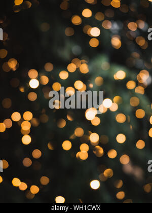 Blurry, golden Christmas fairy lights on outdoor christmas tree at the castle of Nuremberg in the snow during winter creating a beautiful bokeh effekt - Stock Photo