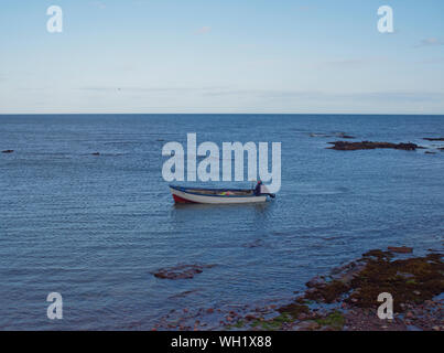 A lone Fisherman preparing to Moor his Small boat off the beach at Tangle Ha on the East Coast of Scotland, near to Johnshaven. - Stock Photo