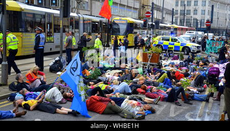 A die-in outside the Arndale Centre as Northern Rebellion protesters, part of the global movement Extinction Rebellion, marched through Manchester, uk, and held a series of die-ins to urge for action on climate change on September 2nd, 2019. Protest sites included Barclays Bank, a Primark store and HSBC Bank. This was the fourth day of a protest which blocked Deansgate, a main road in central Manchester. - Stock Photo