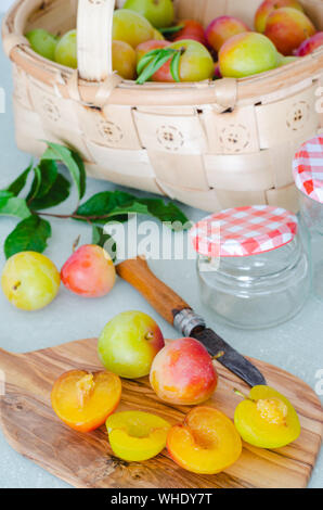 Plums cut on kitchen board. Fresh fruit prepared. - Stock Photo