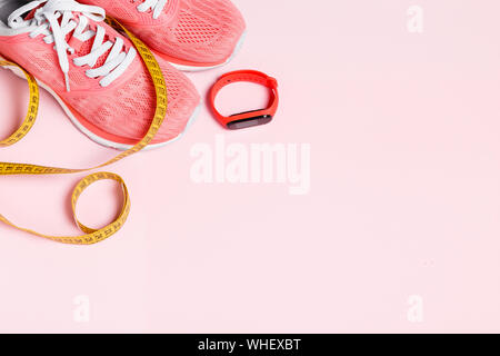Fittnes sport composition with pink sneakers, smart bracelet, measuring tape on pink background. - Stock Photo