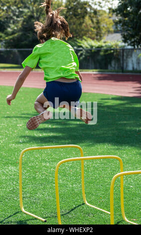 High school teenage girl is jumping over a two foot yellow mini hurdle splitting her feet to the side during track practice. - Stock Photo