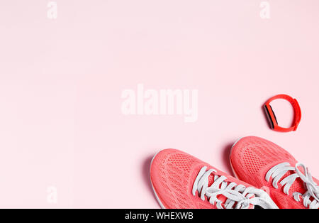 Fittnes sport composition with pink sneakers, smart bracelet on pink background. - Stock Photo