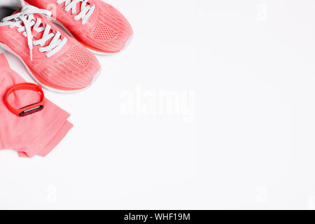 Fittnes sport composition with pink sneakers, smart bracelet on white background. - Stock Photo