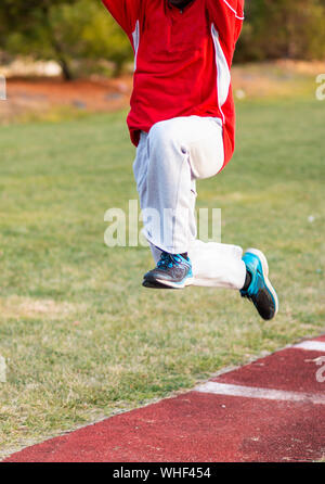 An african american high school boy is practicing the hop, skip and jump phases of the triple jump at track and field practice outside in the winter. - Stock Photo