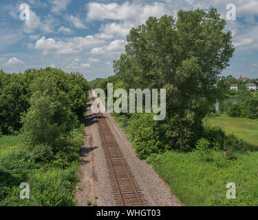 Railroad track running between trees and vanishing in the distance near a village as seen from above on a beautiful summer day. - Stock Photo