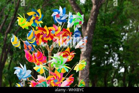 Close up shot at assorted colored pinwheels. Forest background. - Stock Photo