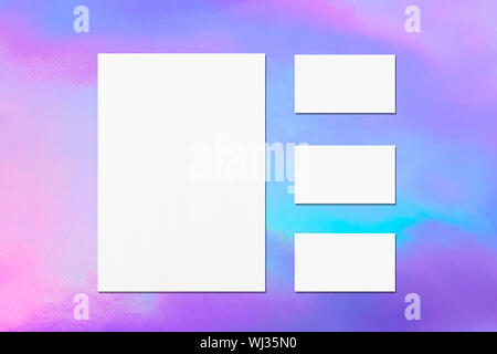 One empty white vertical a4 sized poster and three horizontal rectangle business card mockups with soft shadows on holographic background. Flat lay, t - Stock Photo