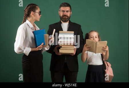 School time of sisters and father in library. Literature lesson and reading grammar book. Education in knowledge day. Teacher man and girls hold book - Stock Photo